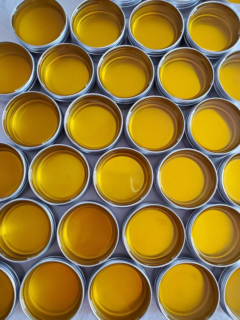 Many 1 ounce metal tins arranged in a honeycomb pattern. The tins are full of lip balm that is still in its golden liquid state.
