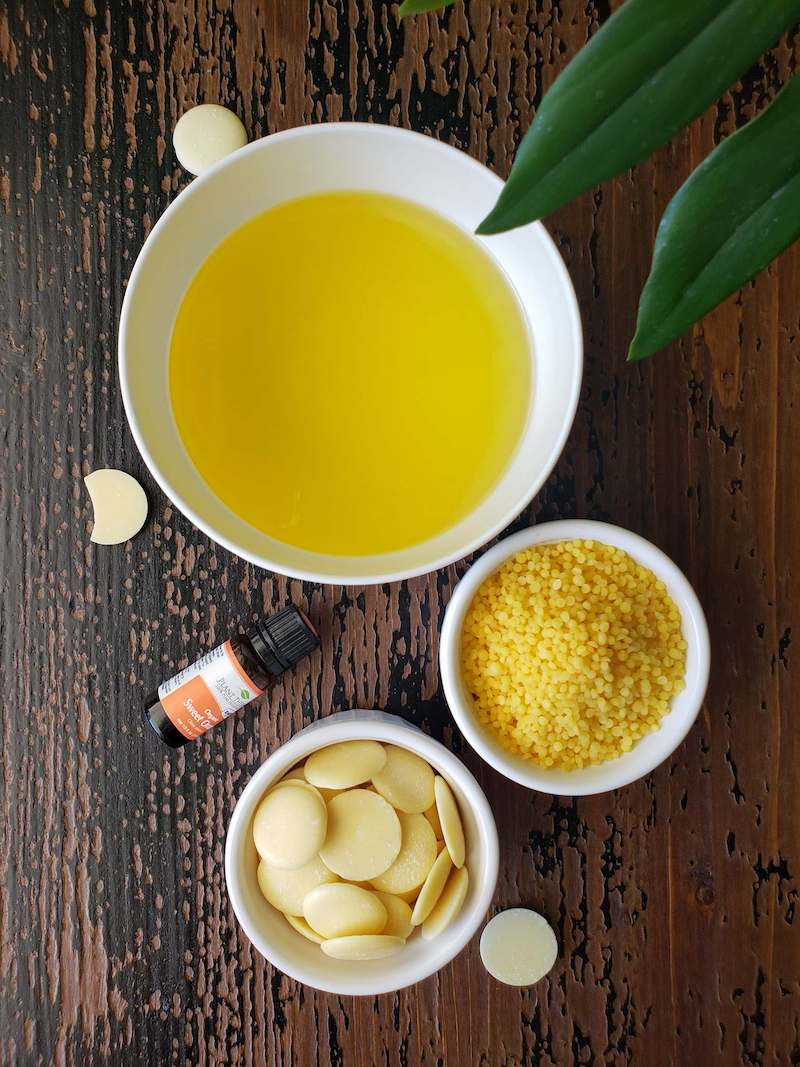 The ingredients for homemade lip balm are shown on a dappled brown and black wooden surface, a white bowl of oil, a white ramekin of beeswax pastilles, and a white ramekin of cocoa butter wafers. There is a smaller bottle of organic sweet orange essential oil next to the ingredients.