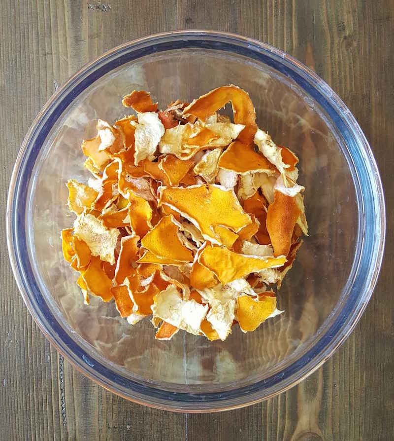 A clear glass bowl is shown from a birds eye view, it contains many dried lemon peels, dried to a crispy perfection. They are slightly darker in color than when fresh, a bit more of a burnt golden orange in color. The back drop is a dark barn wood surface.