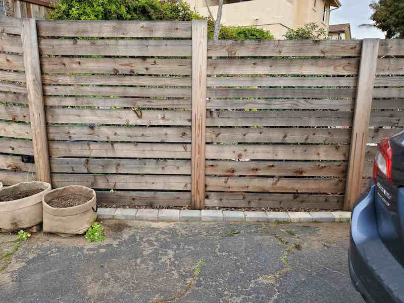 An empty space of pavement that is along the side of a fence. This is a perfect area for a raised garden bed on concrete.