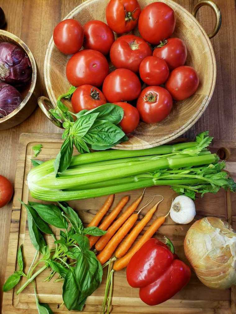 A wood cutting board contains loose carrots, a few sprigs of basil, a whole yellow onion, bulb of garlic, a whole red bell pepper, and a bunch of celery. Above lies a wooden bowl that contains pounds of fresh tomatoes, dark red and glistening in the light. A sprig of basil garnishes the bowl of tomatoes along the side. These are the fresh ingredients that will be used for fresh roasted tomato basil soup.