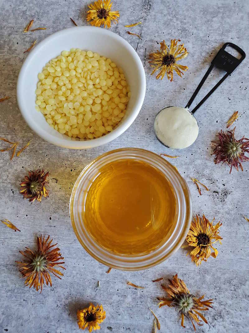 The main ingredients for calendula salve are shown. A white ramekin partially full of beeswax pastilles next to a half pint jar of calendula infused oil, next to a tablespoon measurement of shea butter is shown. There are dried flowers scattered about the area as well.