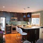 maple wood cabinets in kitchen with white bar stools next to island with white granite countertop cedar floors