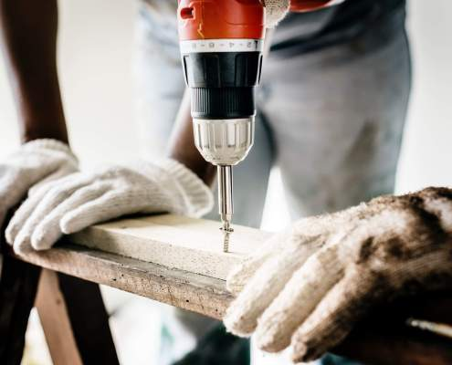 Person using electric drill on a piece of wood for their home improvement project