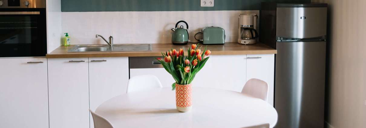 kitchen with clean white details and tulips on the dining table