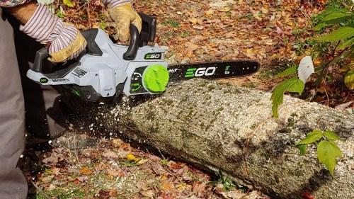 Ego electric chainsaw cutting through a fallen tree