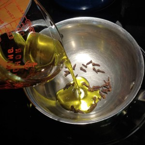 adding oil to cloves to make clove infused oil