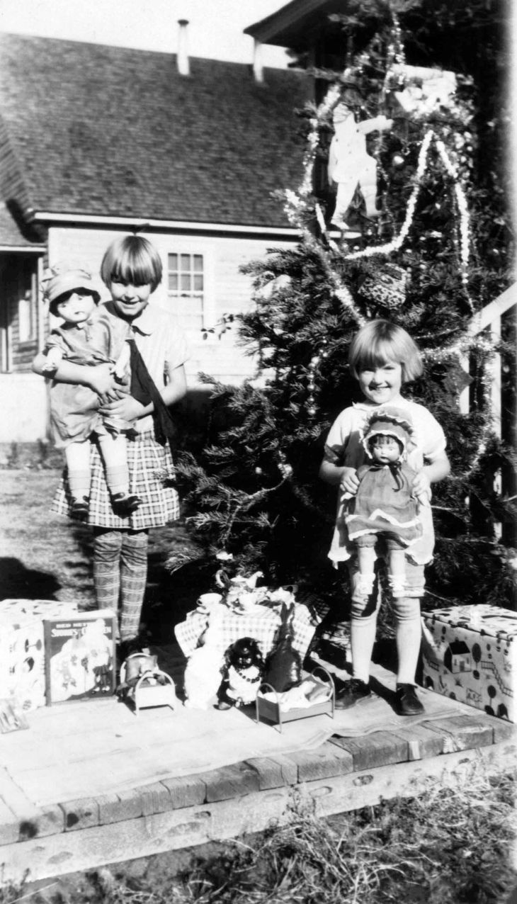 Two Girls With Christmas Presents Outside A Home 2010.304.1.1