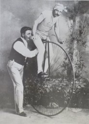 Two high-wheel bicyclists with a penny farthing, 1935.