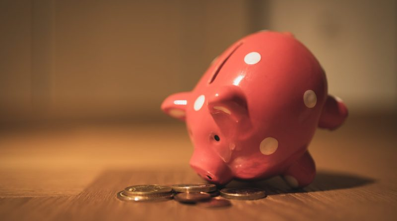 pink pig coin bank on brown wooden table