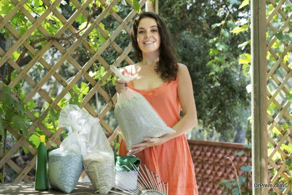 smiling  woman with fertilizer granules in bag at garden