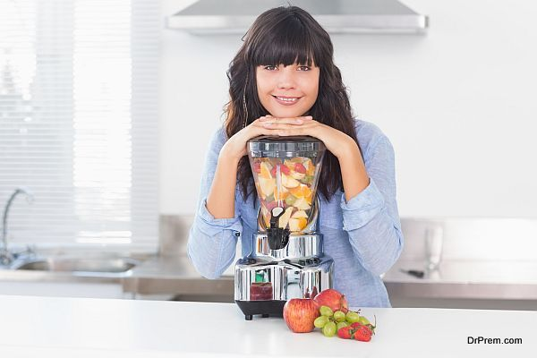 Pretty brunette leaning on her juicer full of fruit
