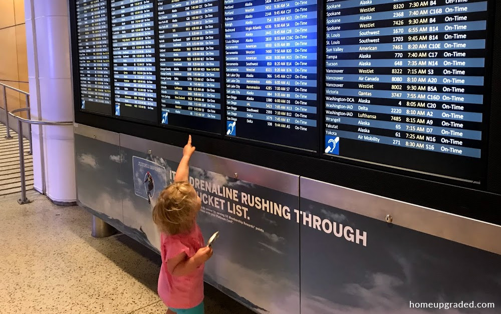 Our toddler daughter points at a large monitor displaying flight times and arrivals.