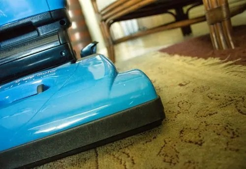 An image of a upright vacuum cleaner on an oriental rug.