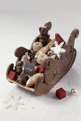 Traîneau gourmandise, Lenôtre En chocolat lait caramel garni de calissons bronze, dominos assortis, nougats assortis, pâtes de fruits en forme de mini kouglofs, sujets en chocolat. 700 g, 98 €. www.lenotre.com