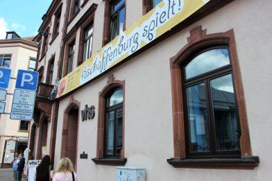 Blick auf die Volkshochschule von Aschaffenburg inklusive Banner von Aschaffenburg spielt