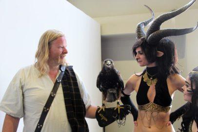 Mann mit Adler auf Arm sowie Frau mit Dämonenhörnern