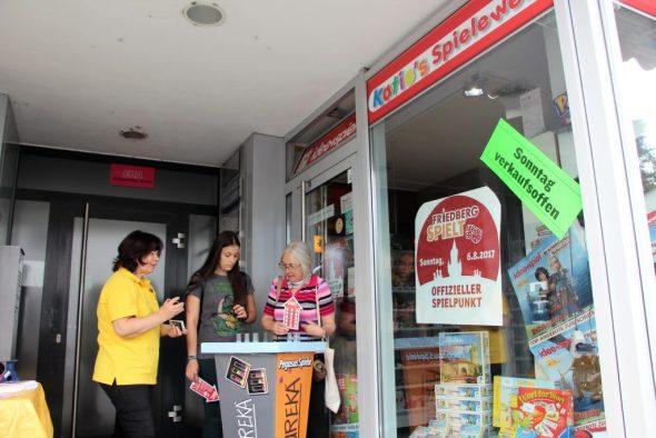 Mama und Jessi vor einem Spieleladen, Dr. Eureka spielend