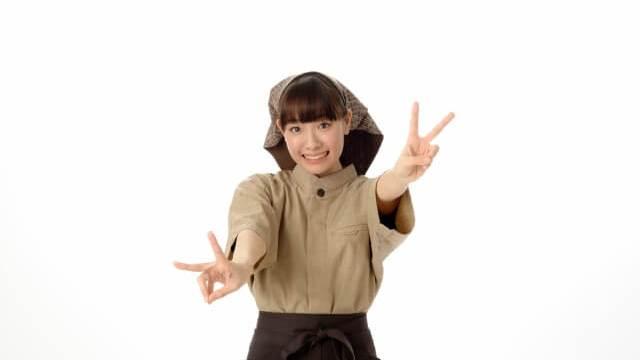 ピースサインをする居酒屋の頭巾女性の画像