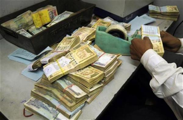An employee arranges Indian currency notes at a cash counter inside a bank in Agartala