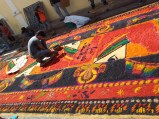 Making the finishing touches on an alfombra. You can see some of the stencils used in the background.