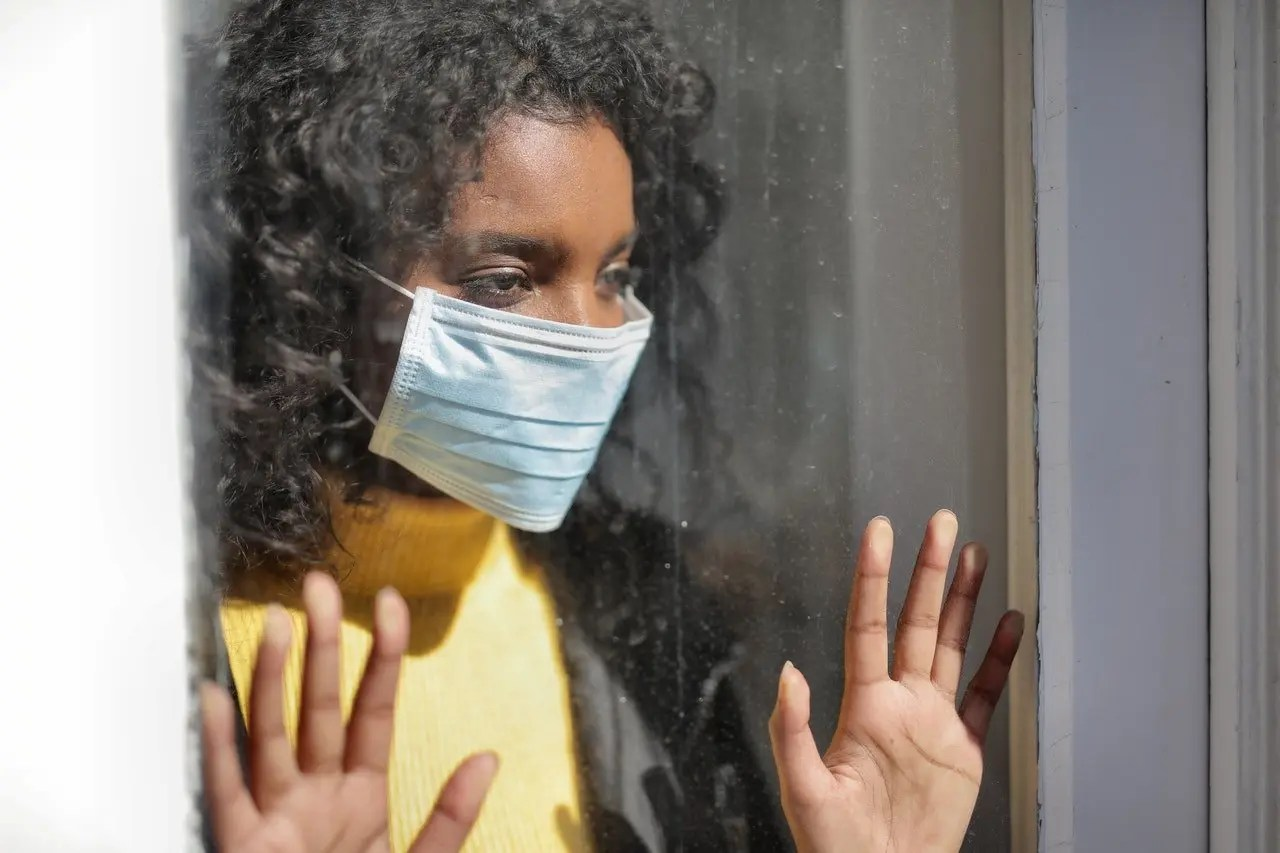 Woman looking out of window with medical mask on