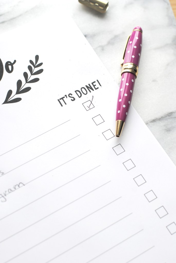 """Close up of the """"It's Done"""" check off column on the to do list with pretty pink pen and gold clip"""