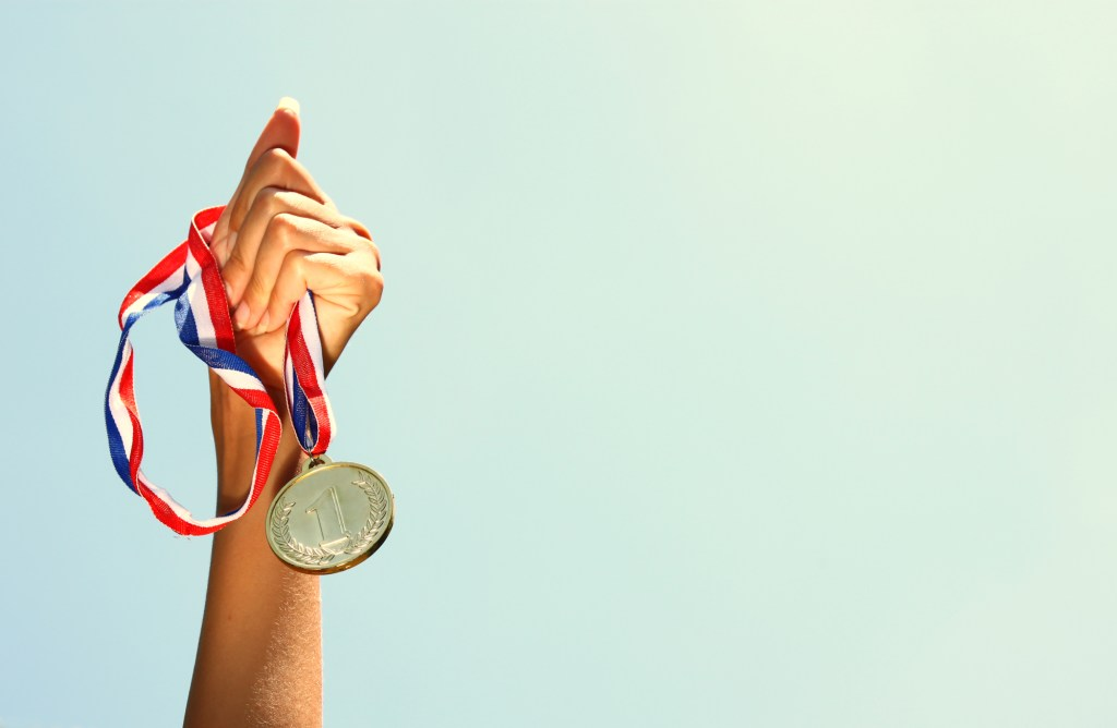 Hand holding up gold medal and clear sky background