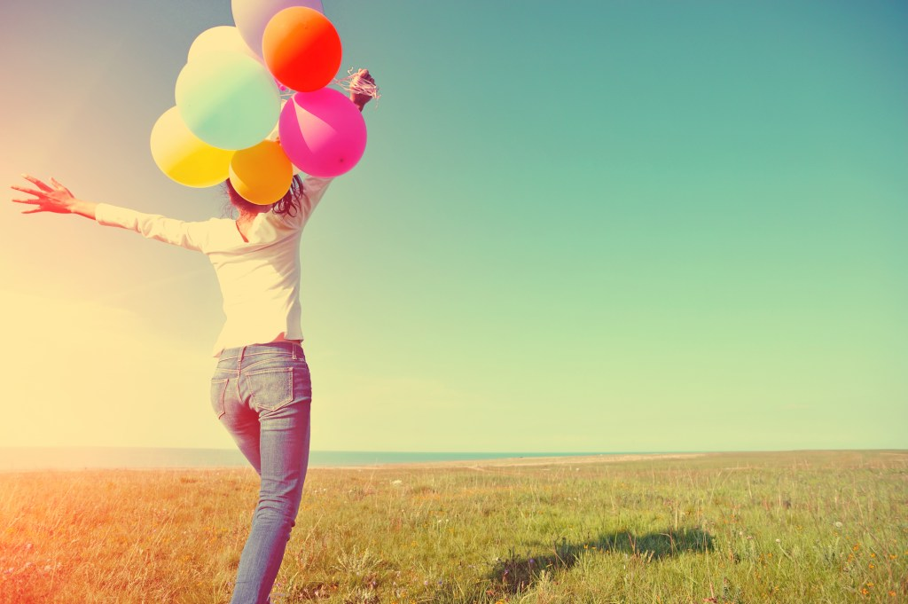 Woman holding bunch of colorful balloons in grassy meadow