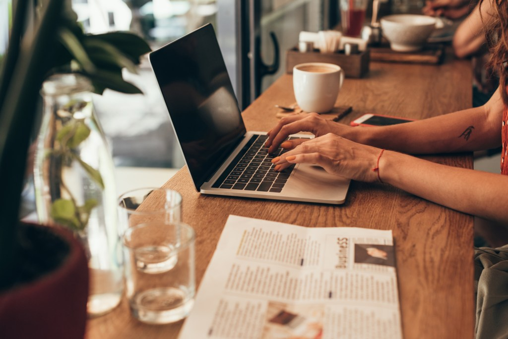 Woman working at laptop in coffee shop working on her blog