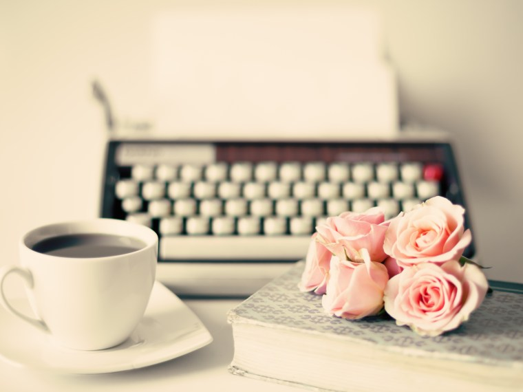 typewriter with coffee and pink roses