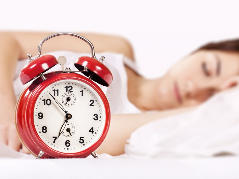 Woman sleeping with red alarm clock in front of her