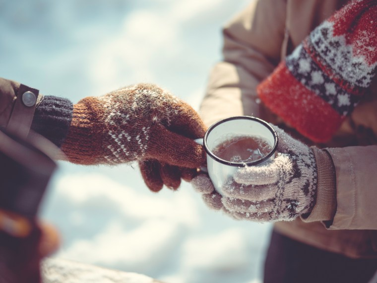 Woman and man sharing coffee mug in winter