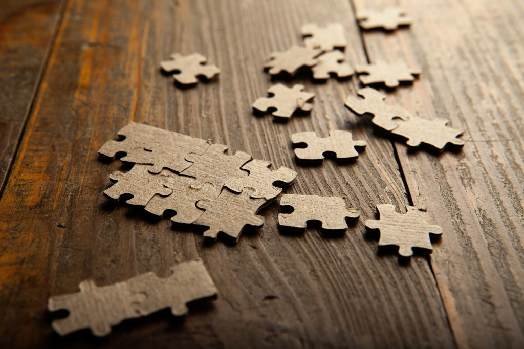 Puzzle pieces scattered on a wooden background