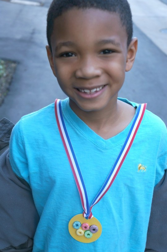 Boy wearing Fruit Loops olympic medal, crafts for kids