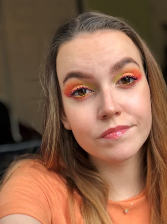 Emily is wearing a Baskin Robbins Rainbow Sherbet inspired eyeshadow look in orange, yellow, and magenta created with the Anastasia Beverly Hills Norvina Mini Volume 2 eyeshadow palette.