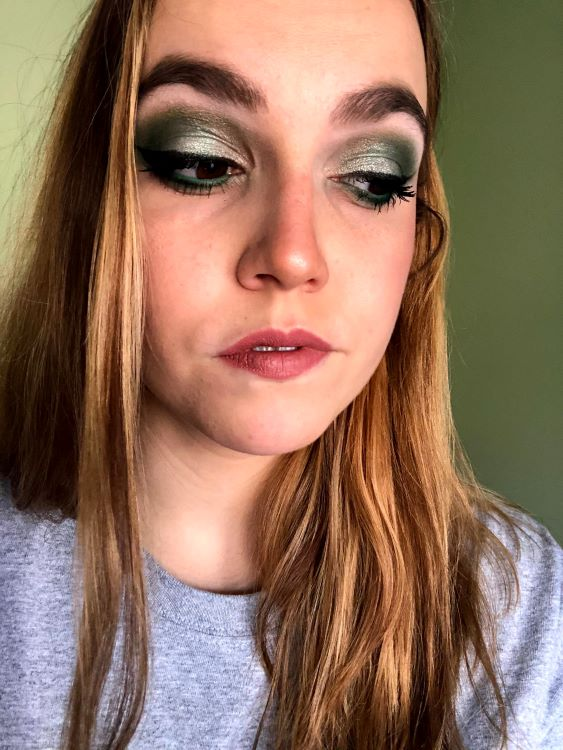 Emily is looking down and off to the side, showing off a shimmery, smoky green eyeshadow look.