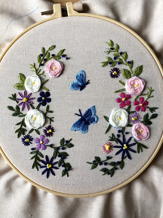 flowers and blue butterflies embroidered on a white fabric background
