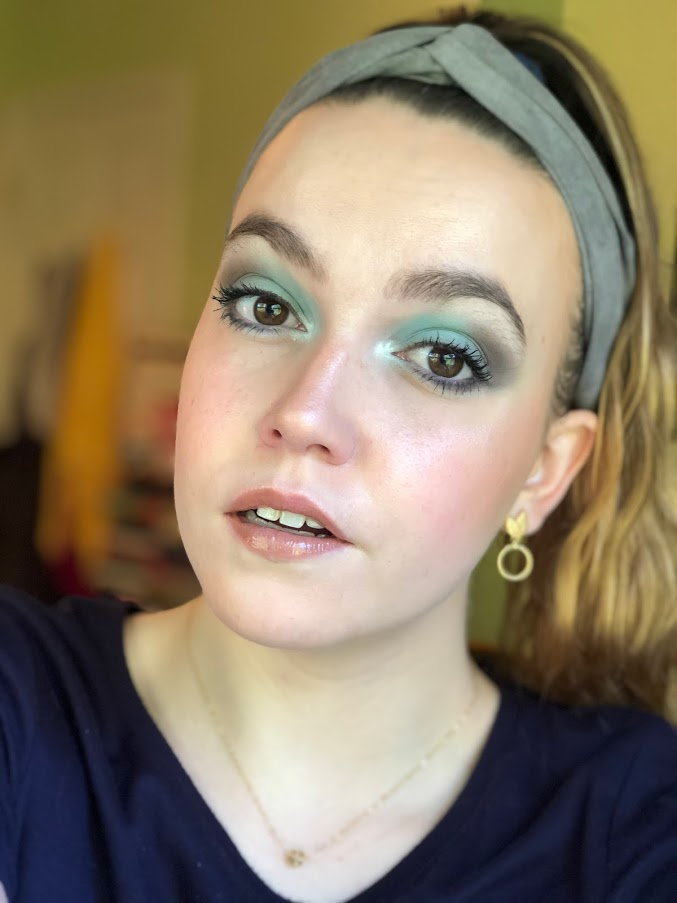 Emily wearing a pastel green and gray eyeshadow look.