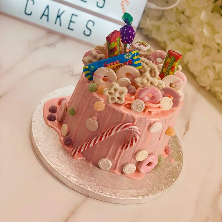 Sweet Mania pink Cake covered in biscuits and sweets