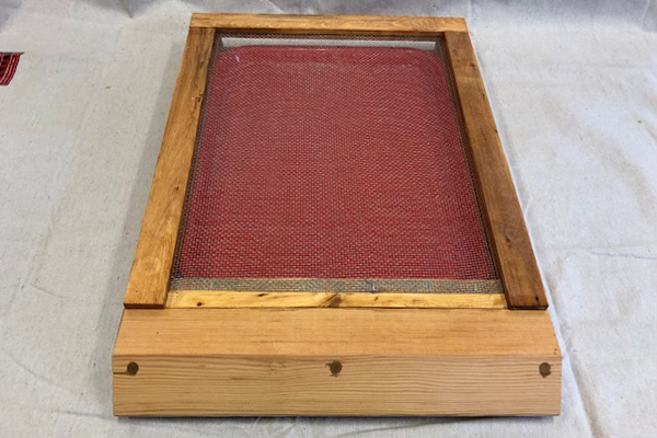 The screened bottom board with small hive beetle tray inserted.