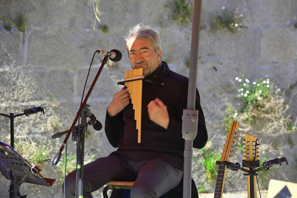 a pan flute player playing the pan flute and relaxing for a few minutes