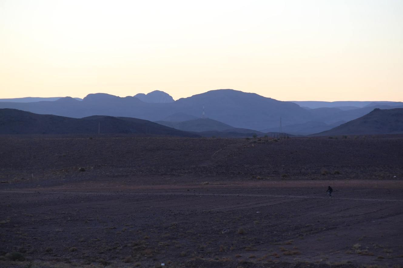 Alba sulle montagne di Ouarzazate con uomo in bicicletta