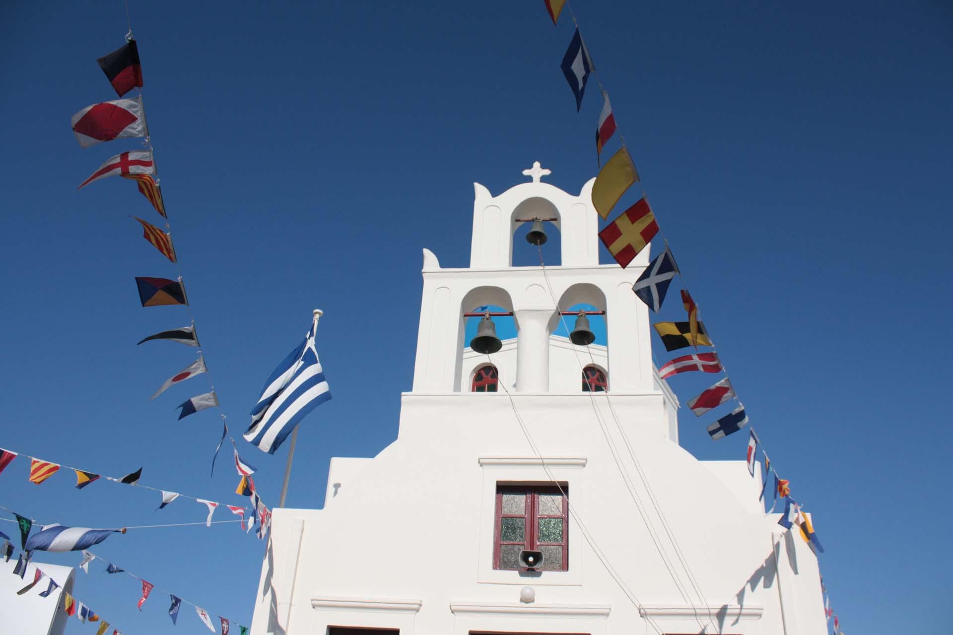Eglise à Santorin avec drapeaux colorés cloches