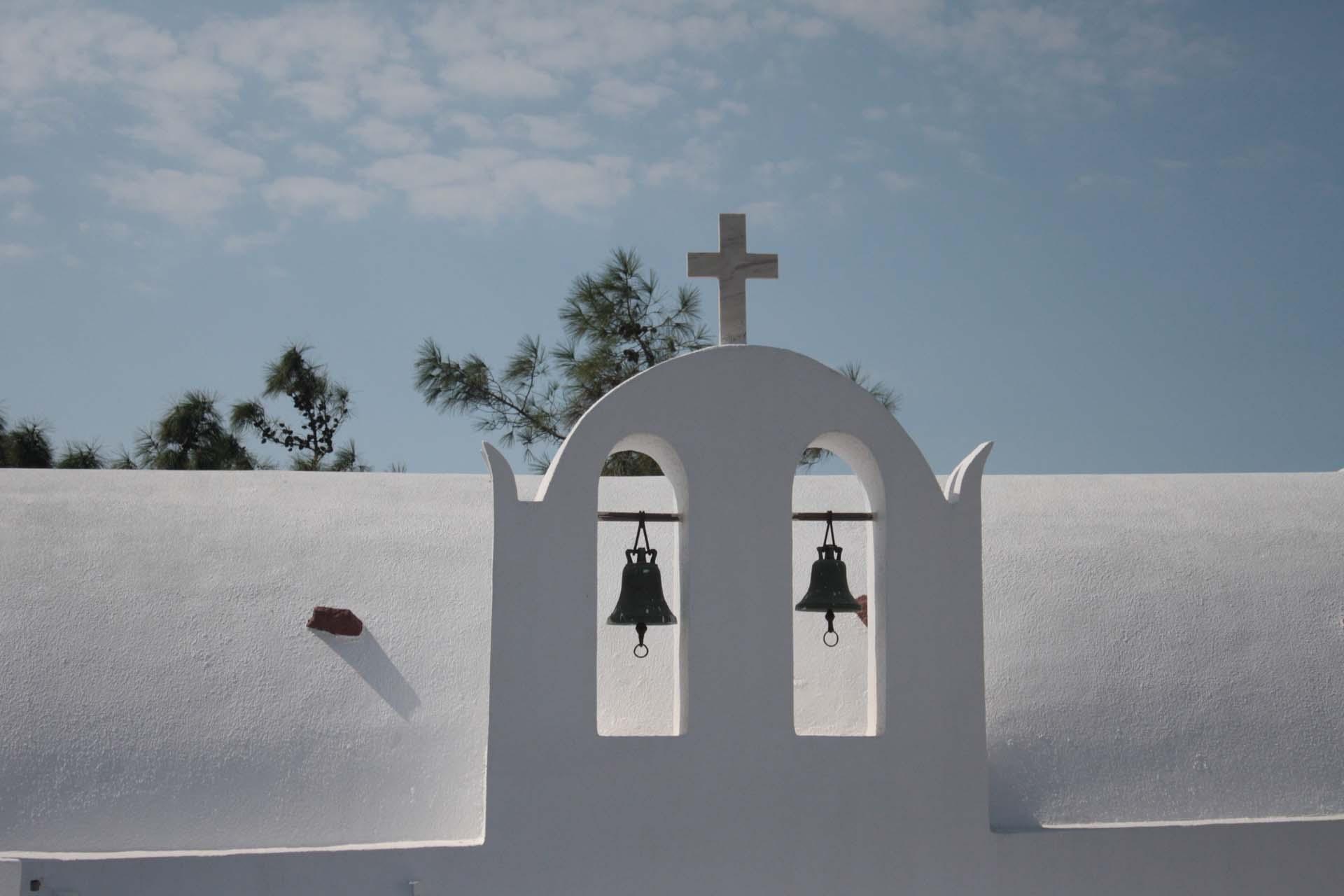 Clocher blanc d'une église à Santorin pins