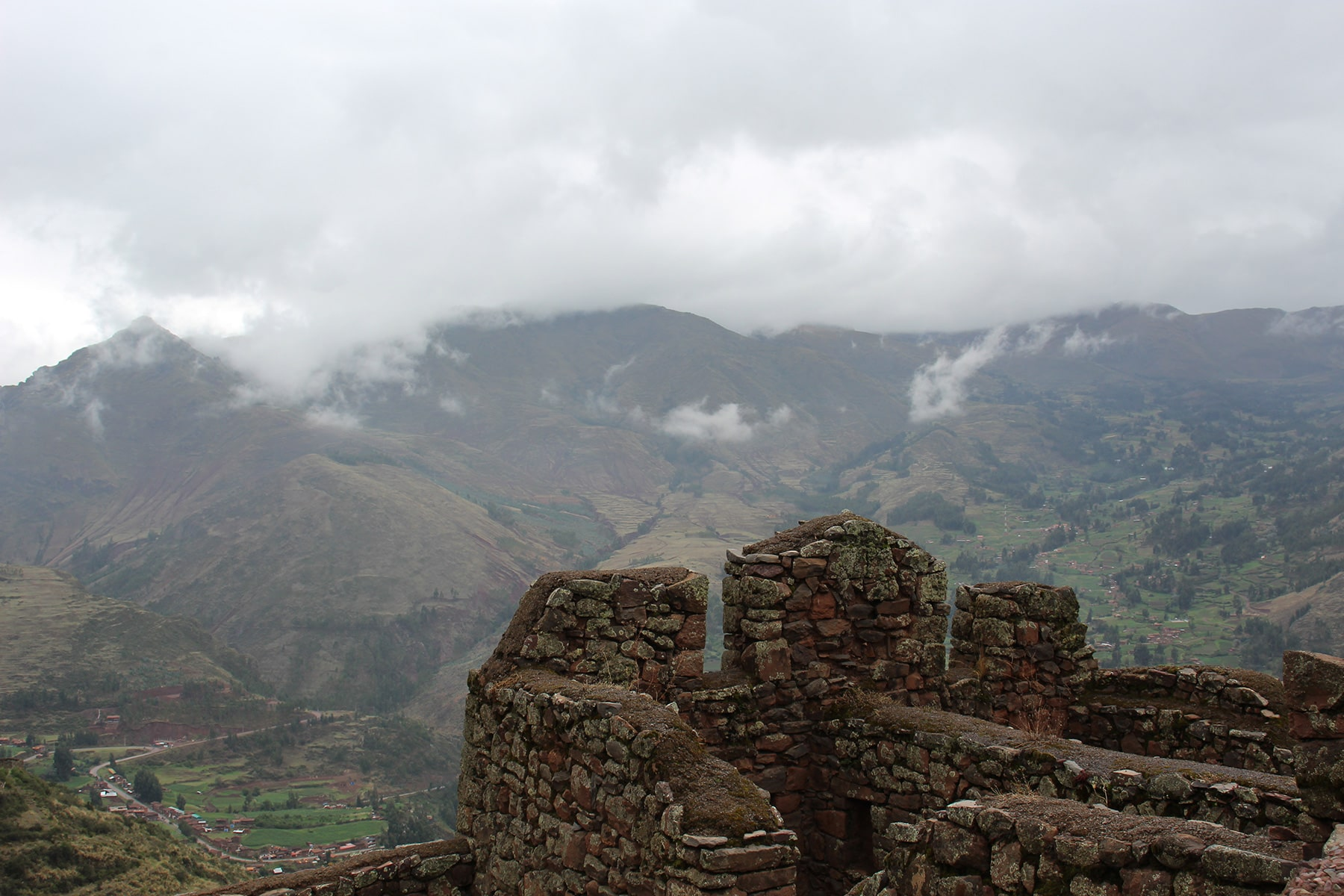 Pisac house ruins facing mountain with clouds