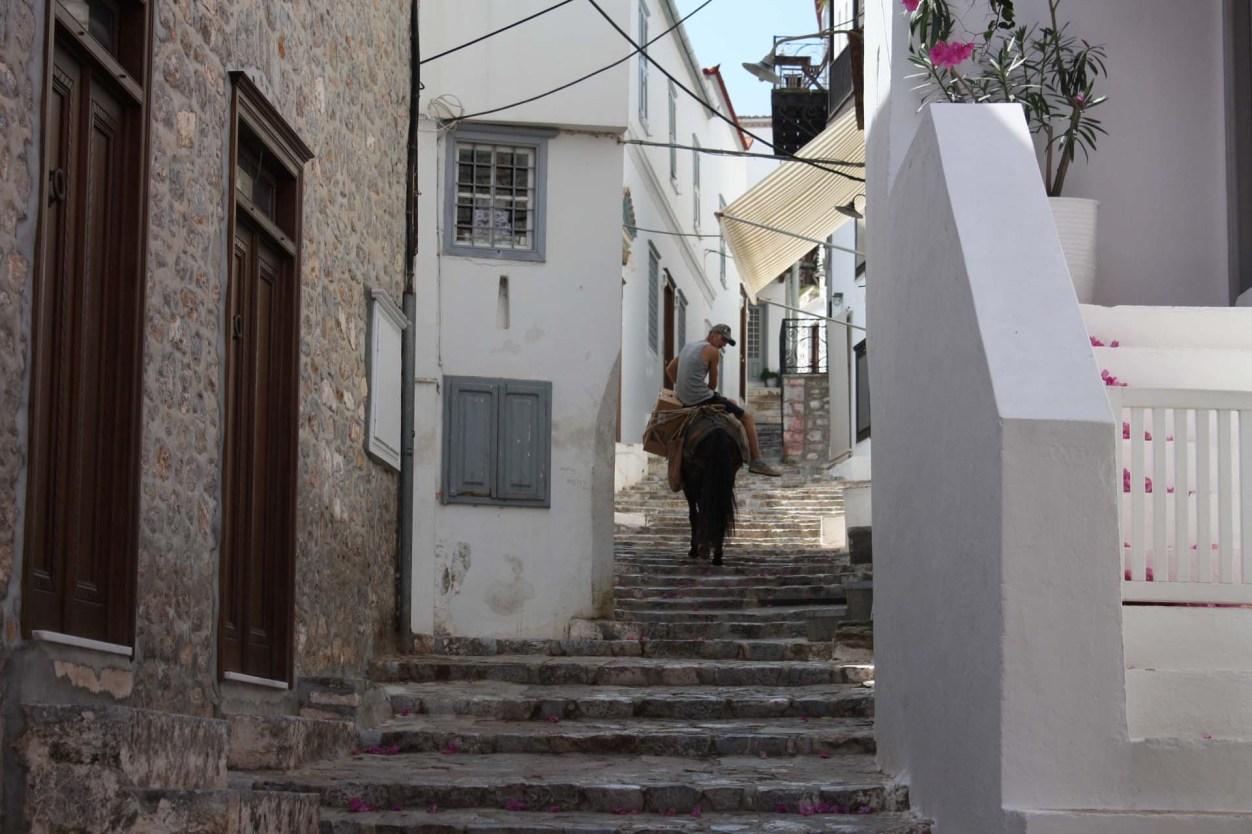 Âne transportant un homme dans une ruelle de l'île d'Hydra
