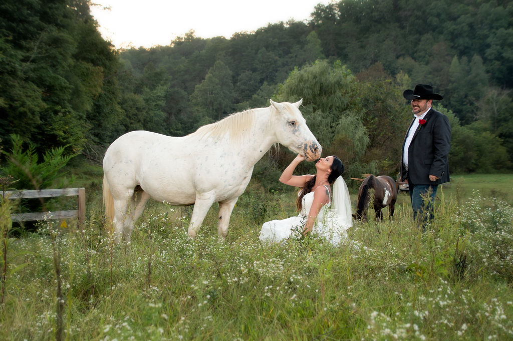 Bride kissing a white horse while her groom in a cowboy hat smiles at them