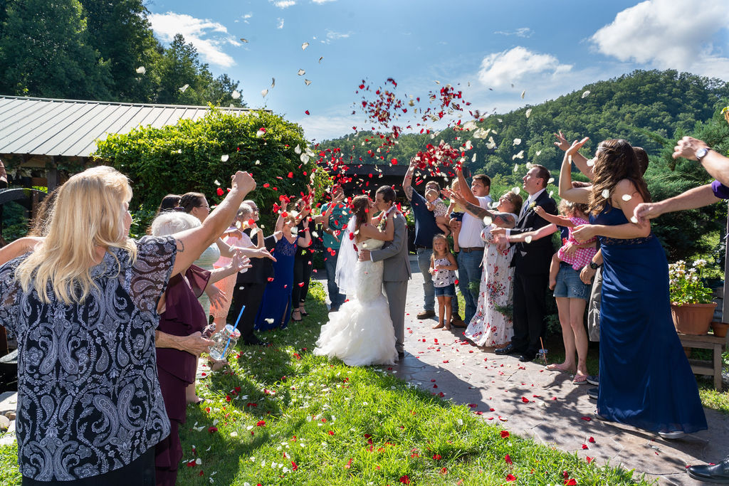 Wedding couple kissing while guests throw rose petals in the summer with a mountain ridge behind them at Honeysuckle Hills
