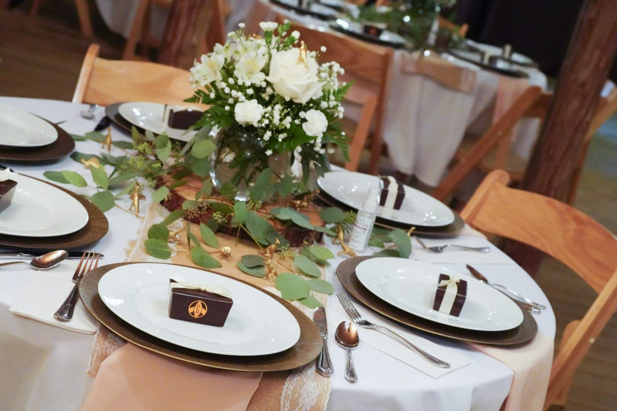 Wedding reception place setting with chocolates and tiny dinosaurs